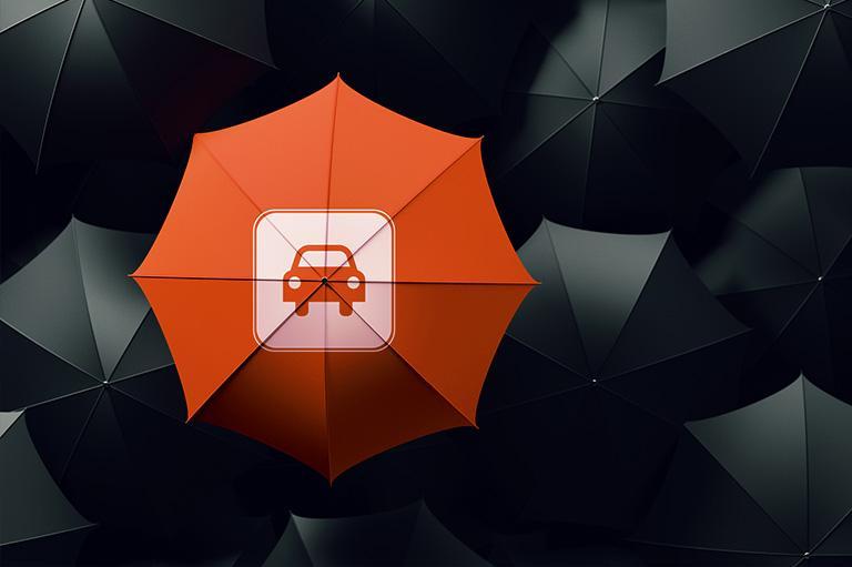 pomarańczowa parasolka zikonką samochodu wśród czarnych parasolek